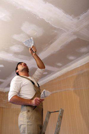 Plasterer working on ceiling
