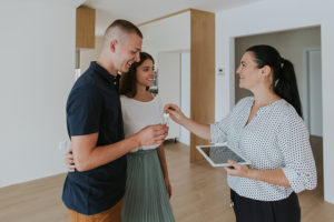 Excited young couple receiving keys to new apartment and smiling towards estate agent.