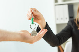 Business, realtor and real estate concept - Hand-to-hand key from new home