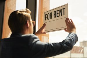 real-estate-agent-hanging-for-rent-sign