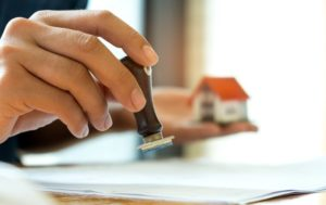 close-up-rubber-stamp-and-model-house-in-hand