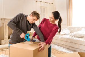 side-view-of-smiling-woman-helping-man-packing