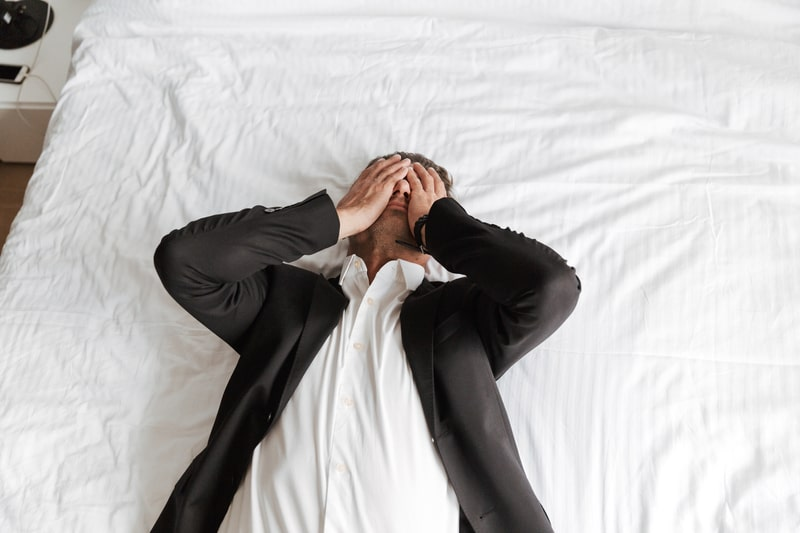 tired-man-dressed-in-suit-lying-on-bed