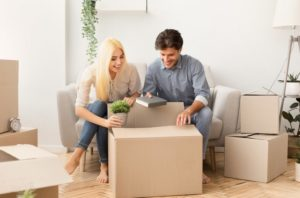 young-man-and-woman-packing-things-in-moving-boxes