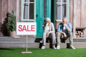 upset senior couple sitting on porch and selling their house, house for sale concept