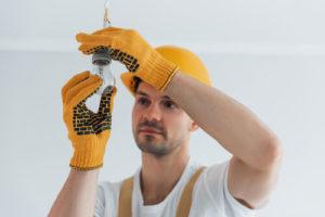 Handyman in yellow uniform changing light bulb. House renovation conception